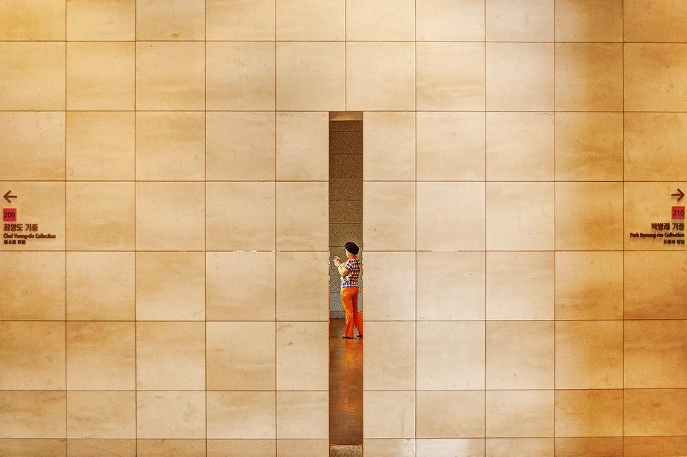 박물관 조형물 틈새로 보이는 사진찍는 아주머니 사진